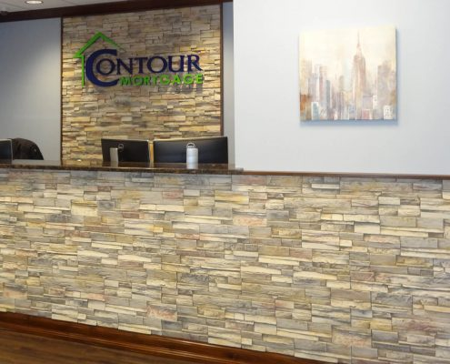 Faux stone in office reception area and behind acrylic logo signage.