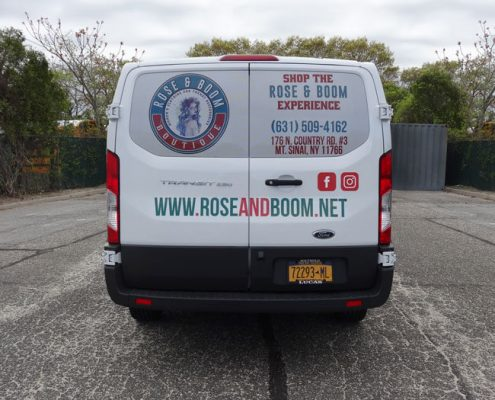 Perforated vinyl on the back window of a van advertises the Rose & Bloom Experience.
