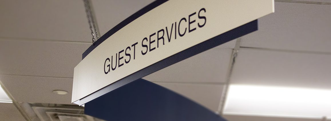 Double paneled suspended Guest Services sign