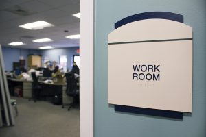 """Cream and blue ADA sign reading """"work room"""""""