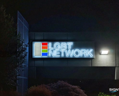 nighttime view of illuminated channel letter sign, front and halo lit, plus logo boxes, on a panel