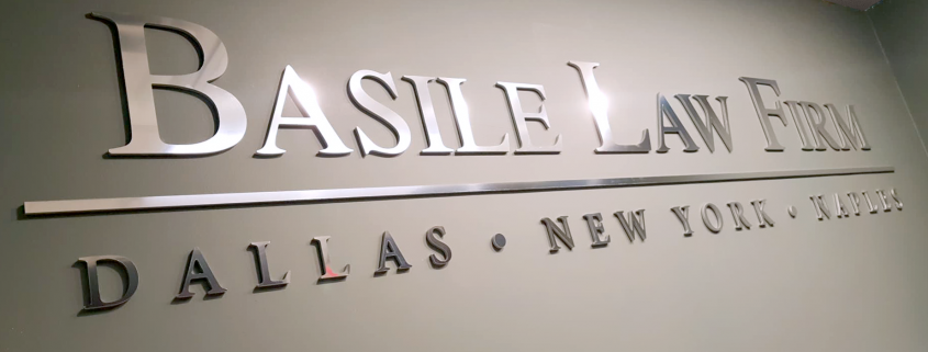 chrome lettering on an interior wall reading Basile Law Firm Dallas New York Naples