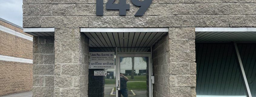black building numbers 149 on an exterior wall